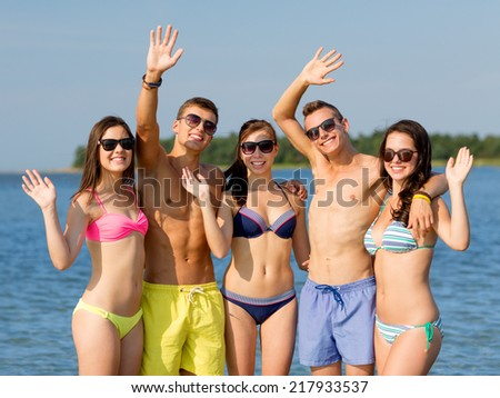 friendship, sea, holidays, gesture and people concept - group of smiling friends wearing swimwear and sunglasses waving hands on beach - stock photo