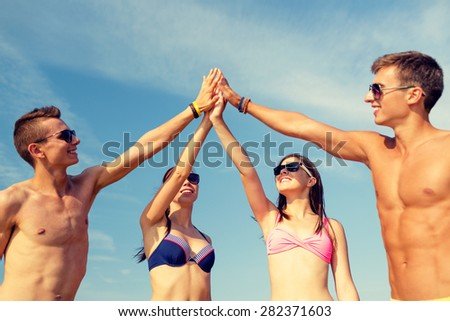 friendship, sea, holidays, gesture and people concept - group of smiling friends wearing swimwear and sunglasses making high five on beach - stock photo