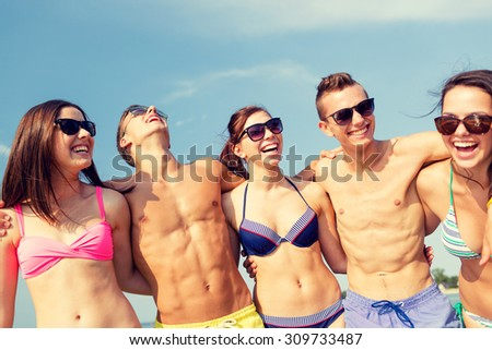 friendship, sea, summer vacation, holidays and people concept - group of smiling friends wearing swimwear and sunglasses talking and laughing on beach - stock photo
