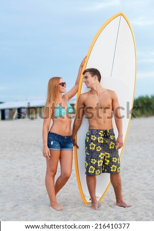 friendship, sea, summer vacation, water sport and people concept - smiling couple in swimwear and sunglasses with surfs on beach - stock photo