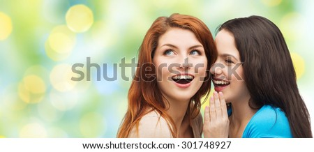 friendship, secrecy and people concept - two smiling girls or young women whispering gossip over green lights background - stock photo