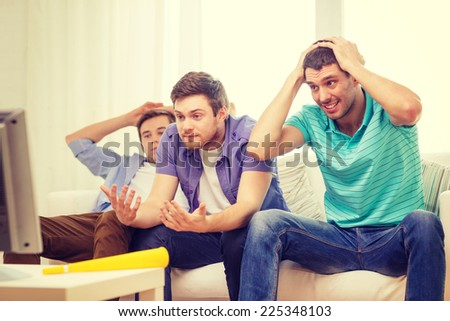 friendship, sports and entertainment concept - sad male friends with vuvuzela watching sports on tv at home - stock photo