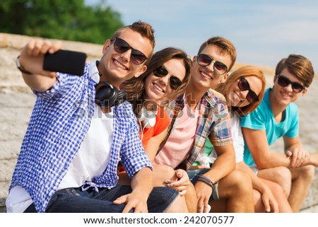 friendship, summer, technology and people concept - group of smiling friends with smartphone and headphones making selfie outdoors - stock photo