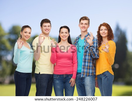 friendship, summer vacation, nature and people concept - group of smiling teenagers showing ok sign over green park background - stock photo
