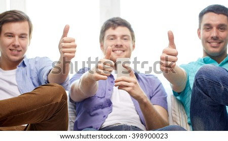 friendship, technology and people concept - close up of happy smiling male friends with smartphones showing thumbs up at home - stock photo