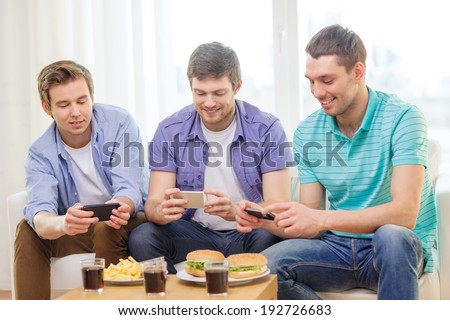 friendship, technology, food and leisure concept - smiling friends taking picture of food with smartphone camera at home - stock photo