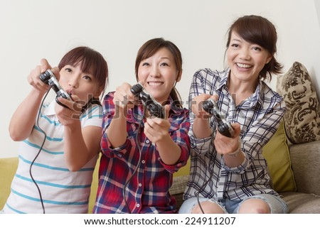 Friendship, technology, games and home concept - smiling female friends playing video games at home. - stock photo