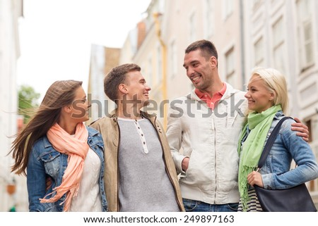 friendship, travel and vacation concept - group of smiling friends walking in the city - stock photo