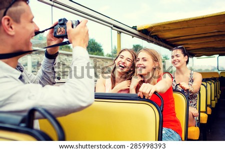 friendship, travel, vacation, summer and people concept - laughing friends with camera traveling by tour bus - stock photo