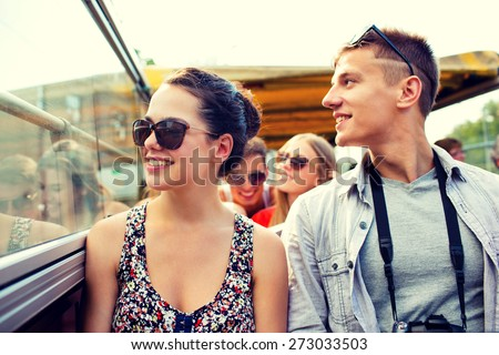 friendship, travel, vacation, summer and people concept - smiling couple with camera traveling by tour bus - stock photo