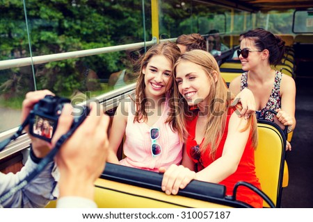friendship, travel, vacation, summer and people concept - smiling friends with camera traveling by tour bus - stock photo