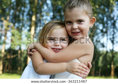 Friendship. Two little girls hugging each other. - stock photo