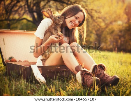 Friendship with an Easter Bunny / Vintage style photo from a beautiful young woman with her bunny - stock photo