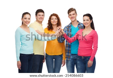 friendship, youth and people concept - group of smiling teenagers making high five - stock photo