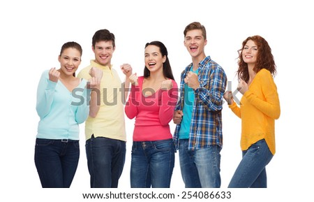 friendship, youth, gesture and people concept - group of smiling teenagers showing triumph gesture - stock photo