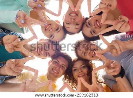 friendship, youth, gesture and people - group of smiling teenagers in circle showing victory sign - stock photo