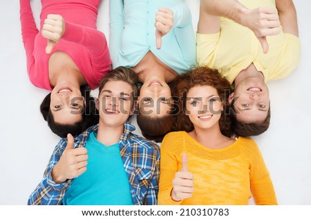 friendship, youth, gesture and people - group of smiling teenagers lying on floor and showing thumbs up - stock photo