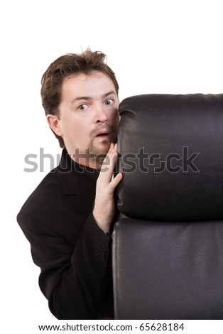Frightened businessman hiding behind a chair - stock photo