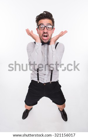Frightened hipster man doen not know what to do. Handsome man in glasses is at a loss isolated on white background. - stock photo
