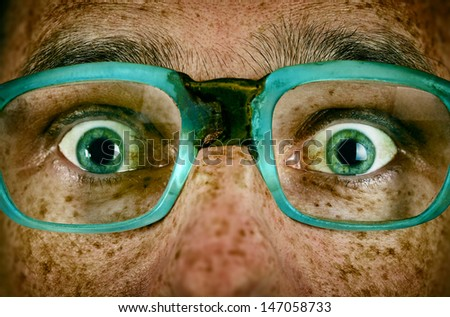Frightened look of a man in old glasses close up - stock photo