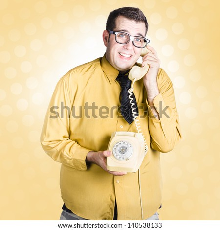 Frightened male staff member talking with look of uncertainty on retro turn-dial telephone. Important phone call concept - stock photo