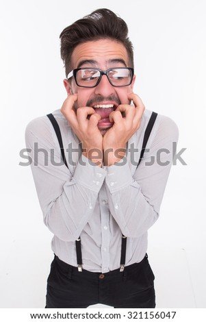 Frightened man in glasses having fear in photo studio. Handsome man in glasses wants to hide somewhere. - stock photo