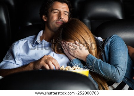 Frightened mid adult woman leaning on man while watching movie in cinema theater - stock photo