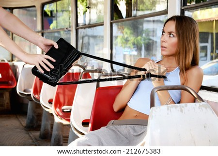 Frightened woman and a thief. Robber stealing a woman's handbag in a train. - stock photo