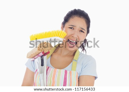 Frightened woman wearing apron holding mop and a broom - stock photo