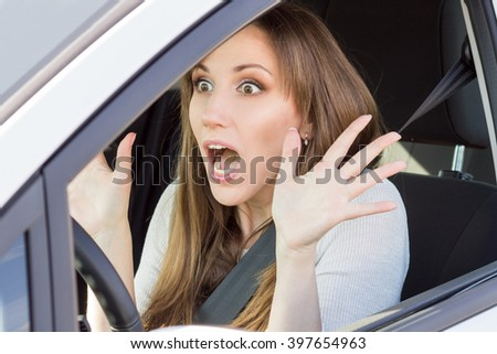 Frightened young car driver woman looking straight ahead. Shocked beauty girl in a car - stock photo