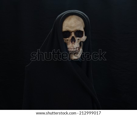Frightening skull wrapped in a black cloth symbolizing death/Death/Eerie lighting conveys fears of death  - stock photo
