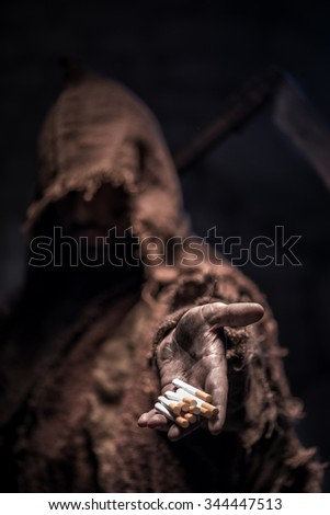 Frightful death character is proposing you a cigarette. He is standing in darkness and waiting for victim - stock photo