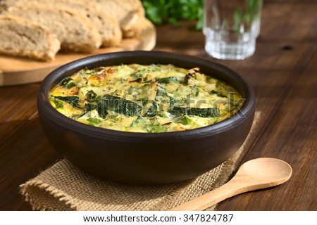 Frittata with zucchini and parsley in rustic bowl, photographed with natural light (Selective Focus, Focus one third into the first frittata) - stock photo