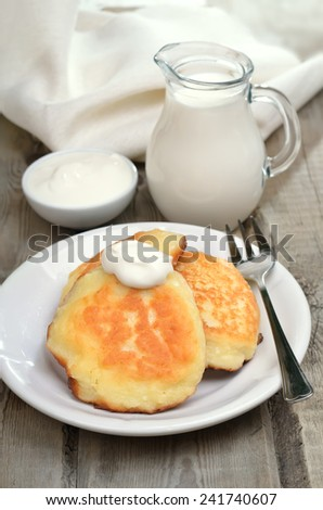 Fritters, milk jug and sour cream on rustic table - stock photo