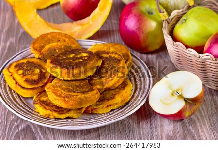 fritters with pumpkin and apples on a beige plate on a wooden background - stock photo