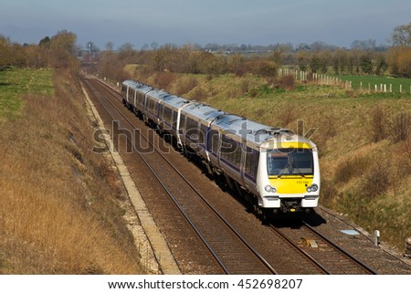 FRITWELL, UK - APRIL 6: A Chiltern Railways operated commuter service from Birmingham heads toward London on April 6, 2015 in Fritwell. Chiltern Rail runs across 336Km of track operating 32 stations - stock photo