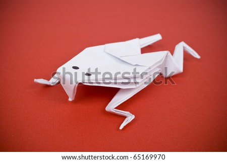 Frog out of paper on a red background - stock photo