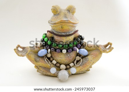 Frog which meditates, meditating frog in jewelry - stock photo