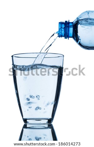 from a bottle of water being poured into a glass, symbol photo for drinking water demand and consumption - stock photo
