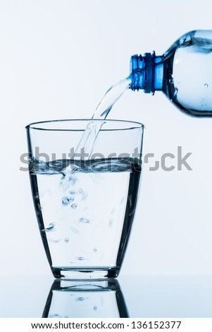 from a bottle of water being poured into a glass, symbolic photo for drinking water, supplies and consumables - stock photo