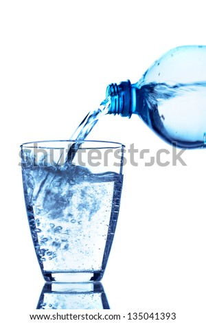 from a water bottle of water being poured into a glass - stock photo