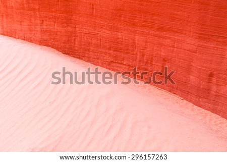 From ancient sand dunes to solid sandstone walls and back again, bright orange rock meets soft cream sand in the American Southwest. - stock photo