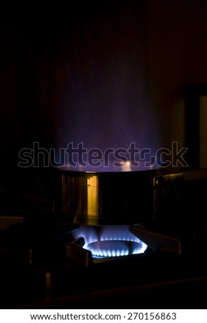 From pan heated spring the flames of burning liquid - stock photo