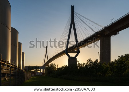 From sunset illuminated Koehlbrand bridge in the harbor of Hamburg. The bridge is an important Cable-stayed bridge and a landmark in Hamburg. It crosses the Elbe river in a height from 315m - stock photo