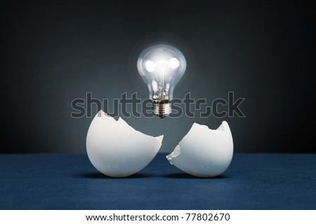From the broken egg the shone lamp is pulled out. - stock photo
