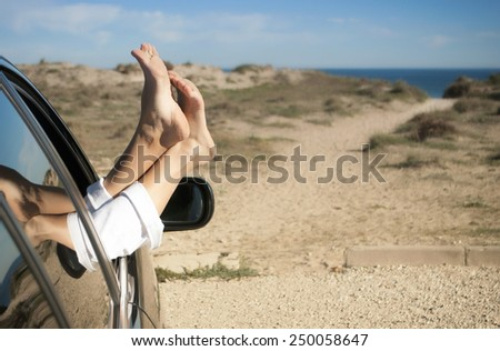 from the car window visible female feet, on the background of the beach - stock photo
