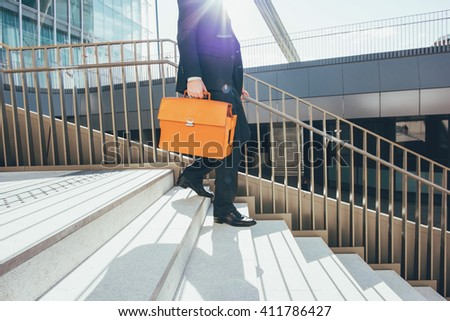 From the neck down view of a contemporary business walking downstairs in the city backlight, holding overnight bag - business, work concept - stock photo
