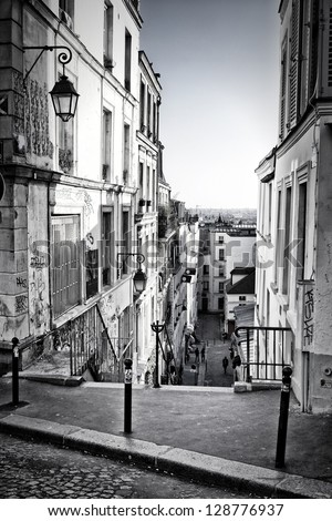 From the top of a typical staircase in Montmartre Hill, we see Paris skyline in the background. Black and white. - stock photo