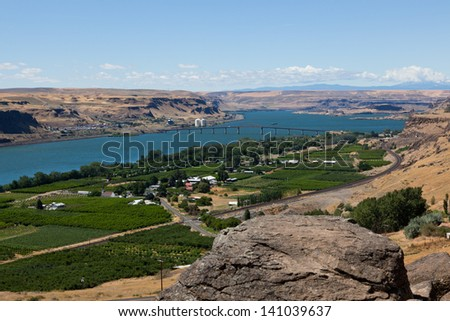 From the Washington state side of the Columbia River gorge looking down on a landscape of green farms, train tracks, and a bridge spanning the river to the Oregon state side in the distance. - stock photo