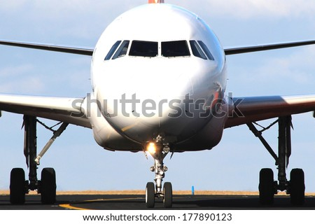 Front close-up view of a white airplane taxiing - stock photo